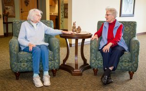 Two residents talking at Majestic Pines in the sitting area