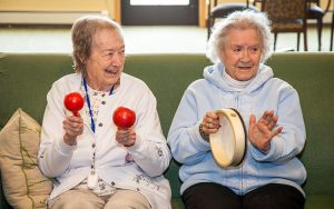 Two residents playing instruments in family room at Majestic Pines