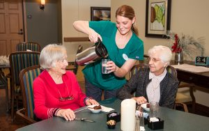 Staff member pouring coffee for two residents at Majestic Pines