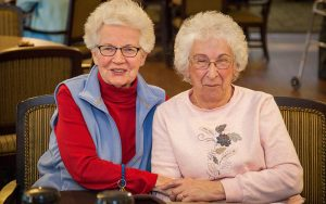 Two residents smiling at camera in dining room of Majestic Pines
